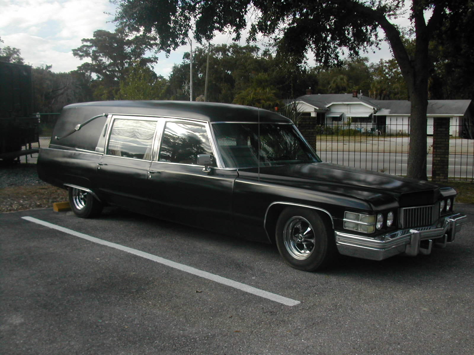 This is a 1974 Cadillac Hearse with a lowered suspension, Edelbrock intake