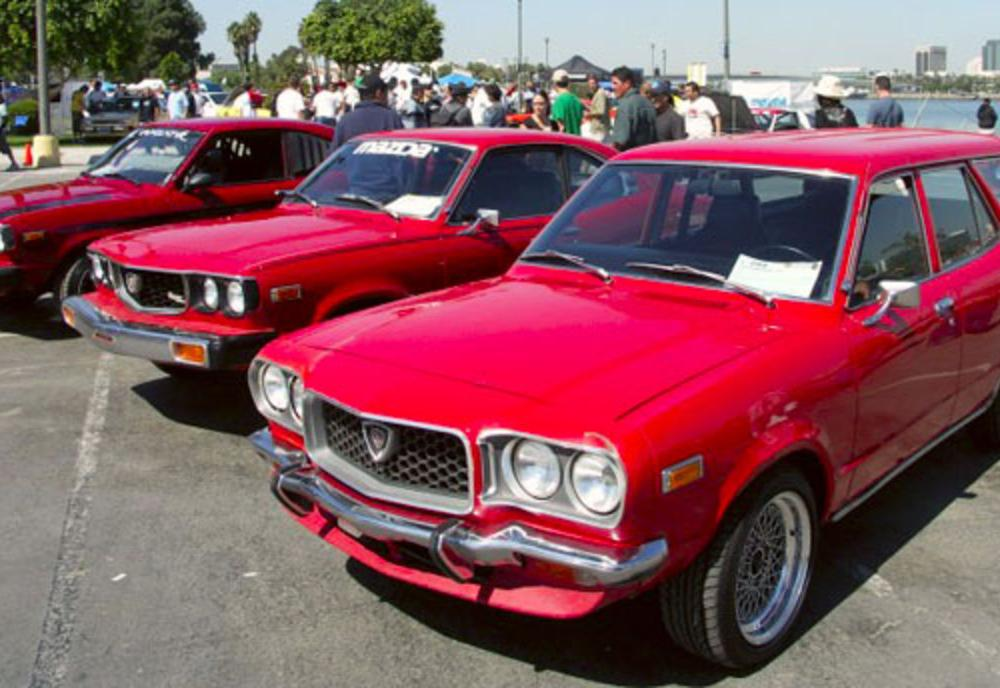A 1973 Mazda RX-3 wagon, with two other Mazdas in the background.